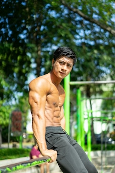 Um homem musculoso asiático nu em uma pose sentada e mostrando seus braços musculosos enquanto está sentado no parque