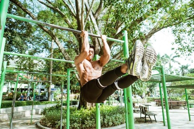 Um homem musculoso asiático sem roupas fazendo exercícios de flexão em l usando uma barra de ferro no parque