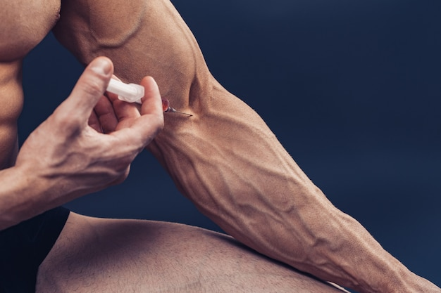 Um homem musculoso com uma seringa