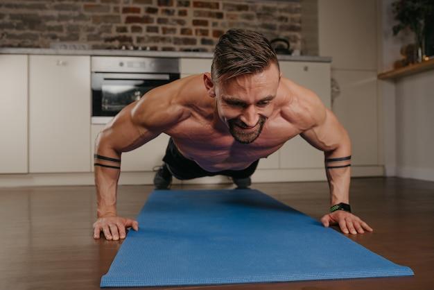 Um homem musculoso e feliz com barba está fazendo flexões em um tapete de ioga azul em seu apartamento à noite