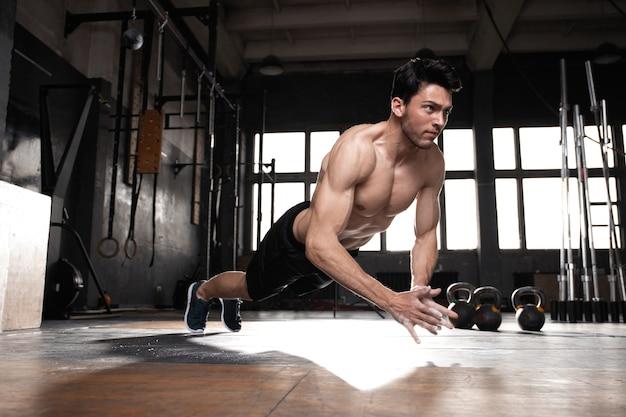 Um homem musculoso fazendo flexões no ginásio crossfit.