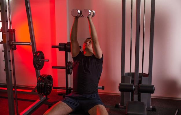 Um homem musculoso levantando halteres enquanto está sentado em um banco no ginásio. linda luz