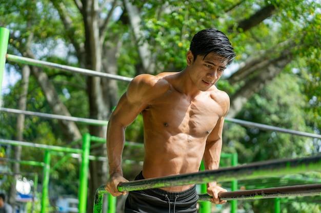 Um homem musculoso que faz flexões para trabalhar os músculos bíceps e tríceps enquanto se exercita ao ar livre em um parque