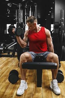 Um homem musculoso sem camisa está fazendo exercícios de bíceps com exercícios com halteres como parte de seu treino de musculação