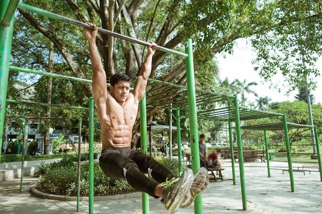 Um homem musculoso sem roupas fazendo exercícios de flexão em l usando barra de ferro no parque