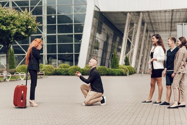 Um homem na companhia de amigos encontra sua namorada com bagagens no aeroporto faz uma oferta para uma garota ruiva