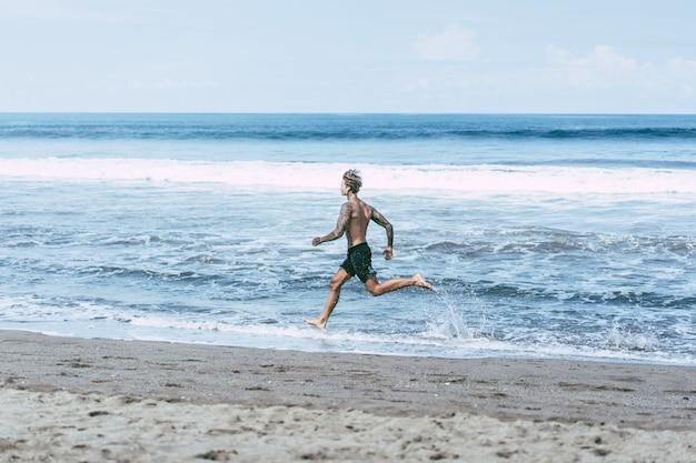 Um homem na costa do oceano correndo ao longo da costa