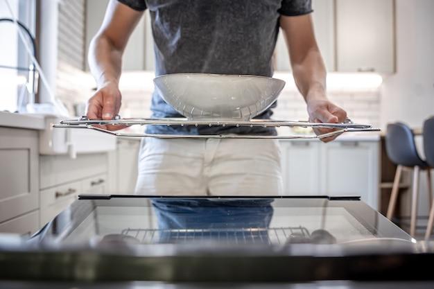 Um homem na frente de uma máquina de lavar louça aberta com um prato.