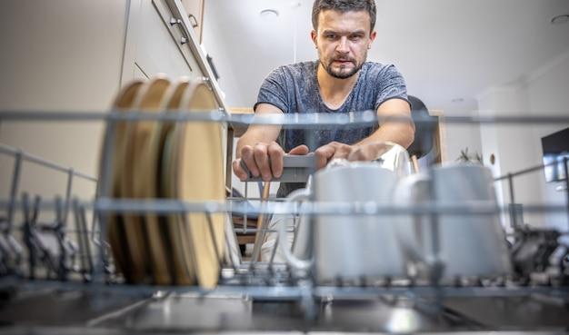 Um homem na frente de uma máquina de lavar louça tira ou põe pratos.