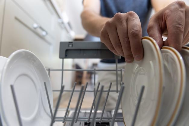 Um homem na frente de uma máquina de lavar louça tira pratos limpos após a lavagem.