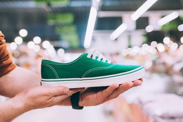 Um homem na loja está escolhendo novos tênis verdes.