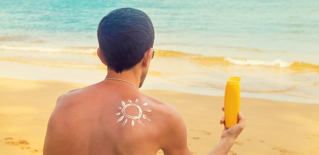 Um homem na praia com protetor solar nas costas