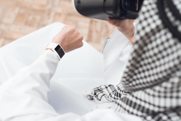 Um homem na roupa árabe thobe olha para o seu relógio de pulso.