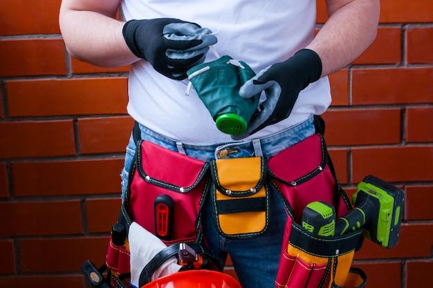 Um homem nas luvas com um respirador na perspectiva de uma parede de tijolo vermelho com um saco cheio para ferramentas.