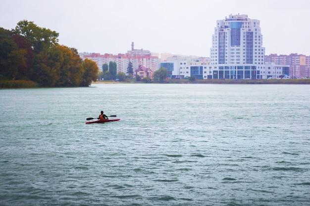 Um homem navegando em um barco (canoa) em um rio em um tempo chuvoso em contraste com os edifícios modernos da cidade
