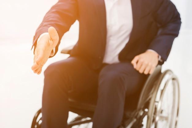 Um, homem negócios, sentando, ligado, cadeira rodas, estender, seu, mão tremer