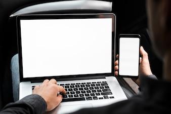 Um, homem negócios, usando computador portátil, e, telefone móvel, com, em branco, tela branca