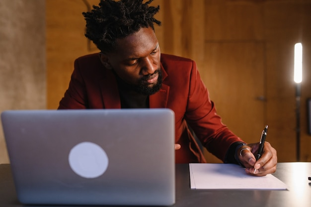 Um homem negro trabalha em um laptop, close-up de suas videoconferências