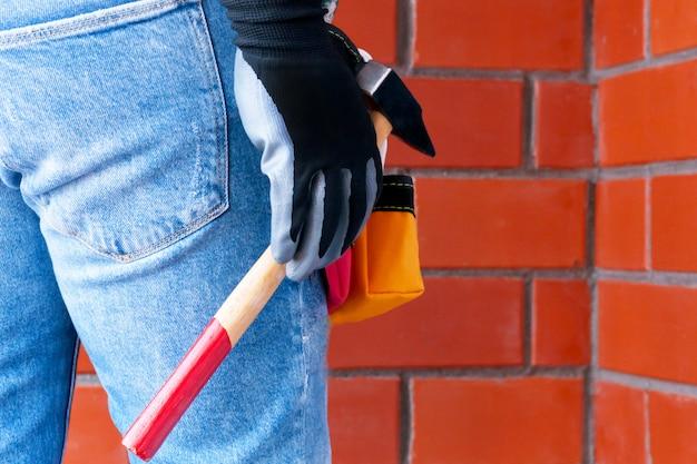 Um homem no contexto de uma parede de tijolo vermelho com um saco cheio de ferramentas.