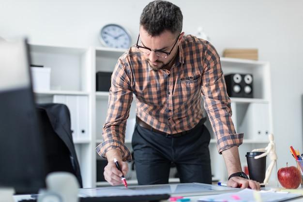 Um homem no escritório está de pé perto da mesa e desenha um marcador no quadro magnético.