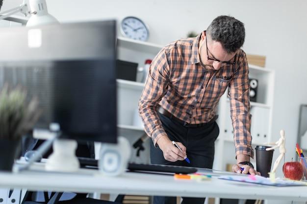 Um homem no escritório está parado perto da mesa e desenha um marcador no quadro magnético.