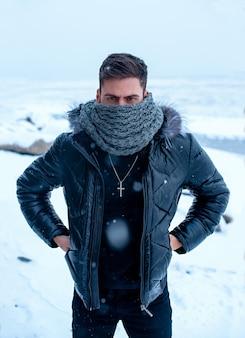 Um homem no inverno em um fundo de neve com roupas pretas