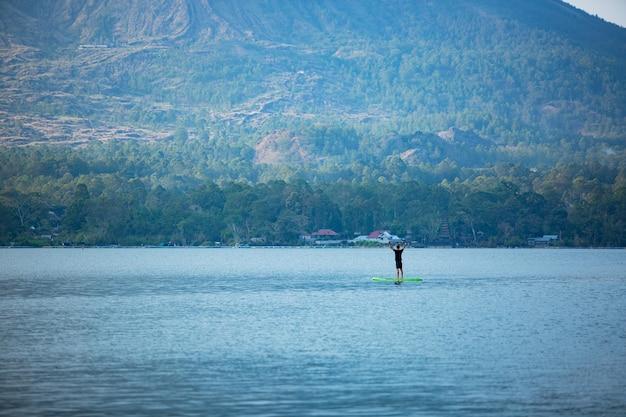 Um homem no lago monta uma prancha de supino.