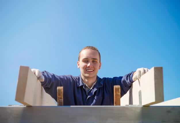 Um homem novo de sorriso nas luvas e na roupa de trabalho está construindo um telhado.