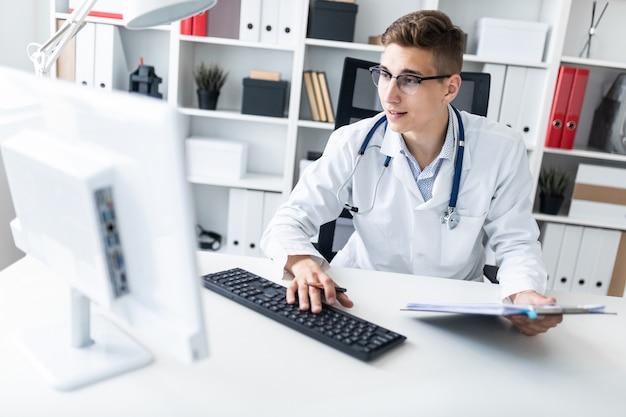Um homem novo em uma veste branca que senta-se em uma tabela no escritório. ele segura uma caneta na mão e trabalha com um computador.