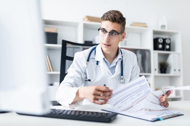 Um homem novo em uma veste branca que senta-se em uma tabela no escritório.
