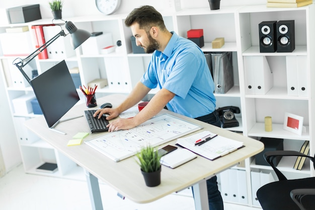 Um homem novo que está no escritório em uma mesa do computador e que trabalha com uma placa magnética.