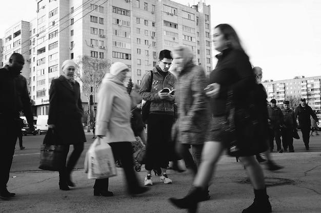 Um homem novo que prende um livro aberto, povos que andam em torno dele. indivíduo elegante de ninhada que lê um livro em uma rua aglomerada. foto preto e branco.