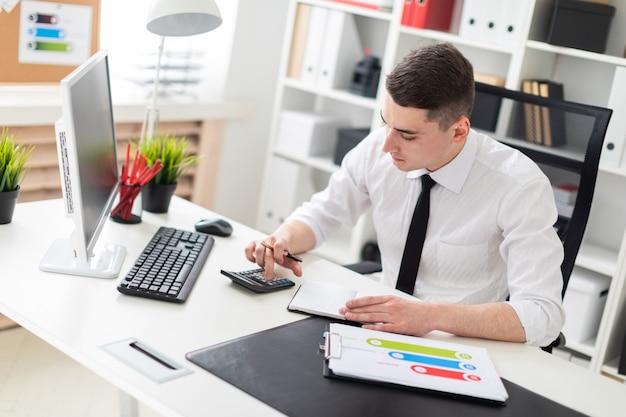 Um homem novo que senta-se em uma mesa do computador no escritório e que trabalha com originais.