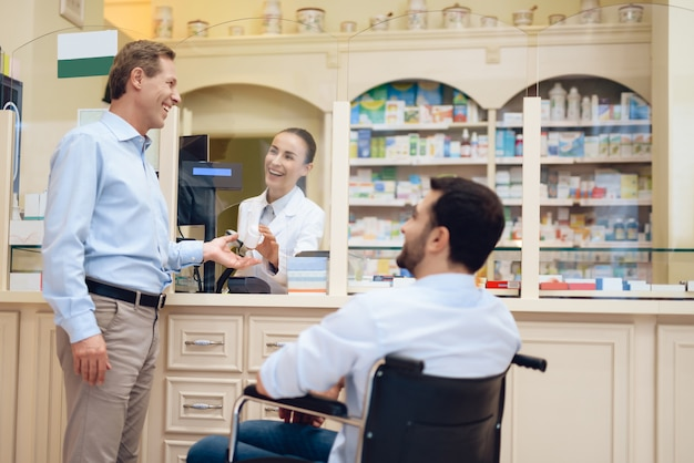 Um homem numa cadeira de rodas está numa farmácia.
