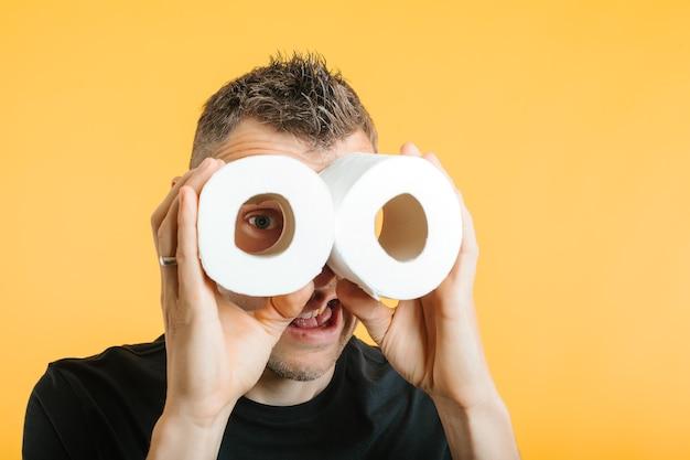 Um homem olha através do papel higiênico na esperança de acabar com o coronavírus covid-19