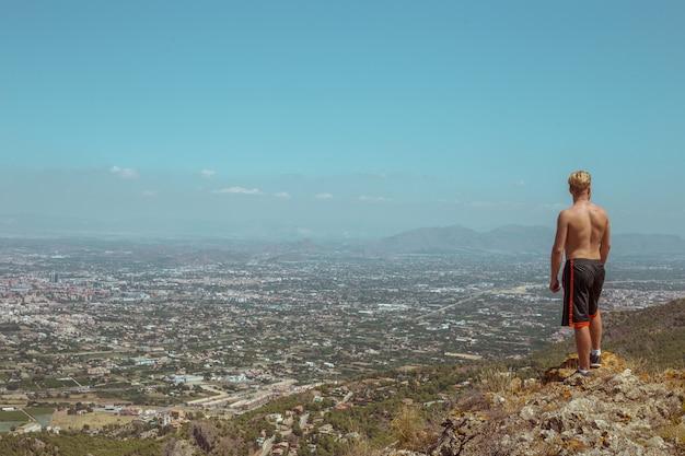 Um homem olha para a cidade da beira do penhasco