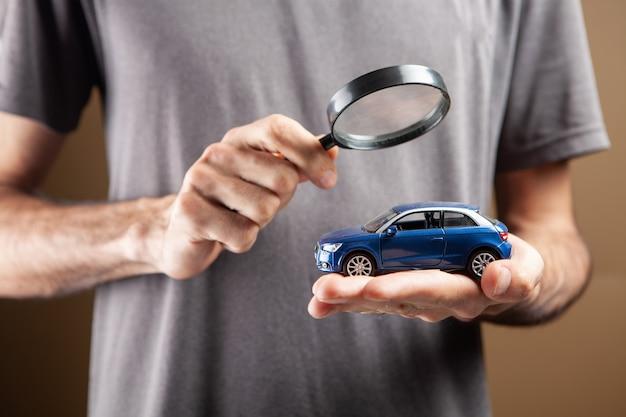Um homem olha para o carro com uma lupa. conceito de busca de carro