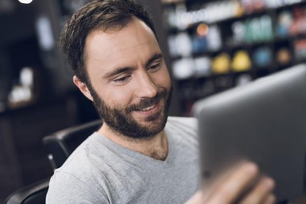 Um homem olha para tablet na cadeira de barbeiro na barbearia do homem.
