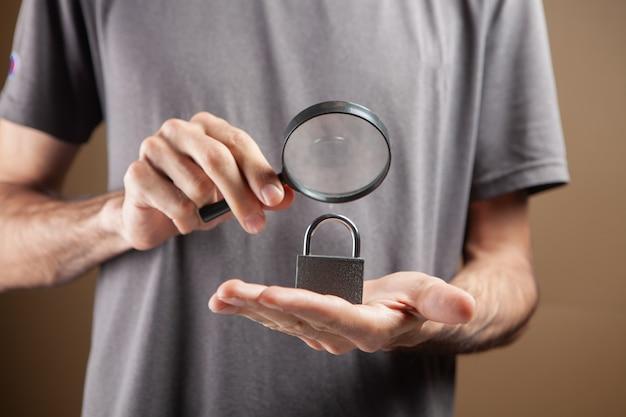 Um homem olhando para a fechadura com uma lente de aumento. estudo do conceito de proteção. buscando proteção em fundo marrom