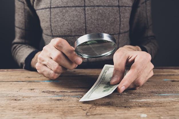 Um homem olhando para dinheiro com uma lupa