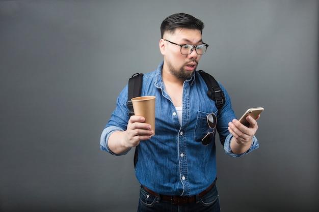 Um homem olhando para o telefone com espanto