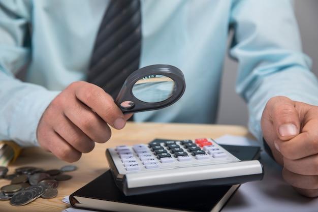 Um homem olhando para uma calculadora com uma lupa