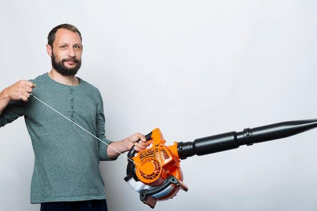 Um homem operando o motor puxa o cabo de uma ferramenta de ventilador de ar