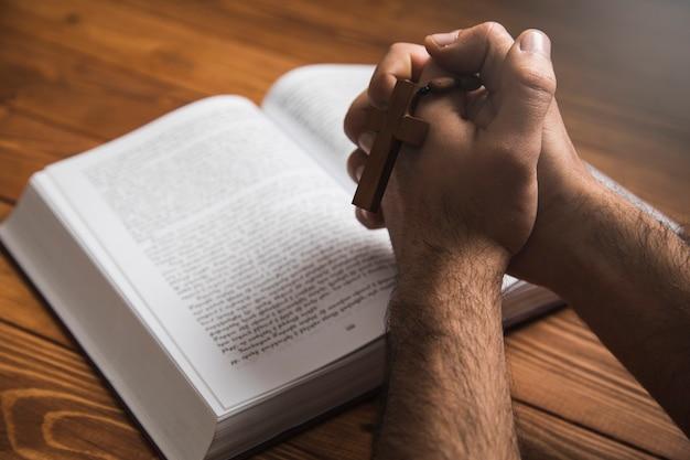 Um homem orando em um livro em uma superfície escura