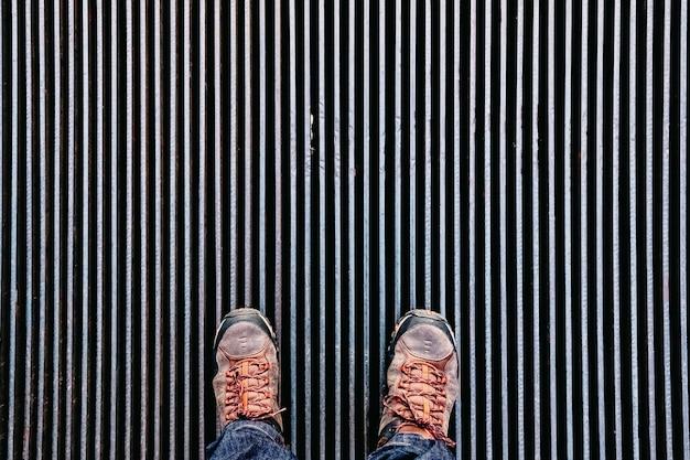 Um homem para em uma placa de ventilação em linhas escuras e olha para baixo.