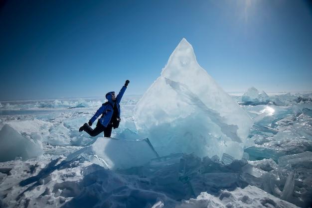 Um homem parado em um bloco de gelo quebrado no lago congelado baikal