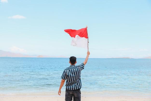 Um homem parado na praia acenando uma bandeira da indonésia com fundo de paisagem marinha