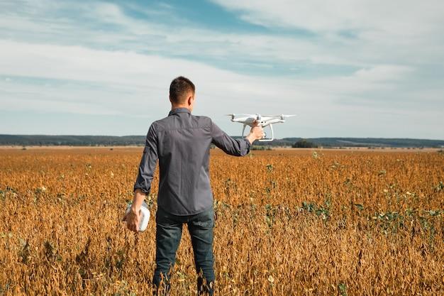 Um homem parado perto do carro lança um drone. voo do drone em campo amarelo