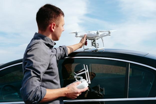 Um homem parado perto do carro lança um drone