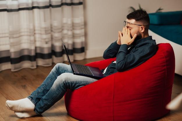 Um homem parece muito cansado. jovem gerente cansado sentado em casa com as mãos nos olhos, estando com sono e exausto.